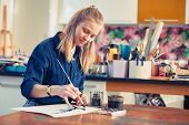 Young Woman Artist Working On Painting In Studio. Selective Focus On Foreground. poster