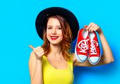 Portrait Of Young Smiling Red-haired White European Woman In Hat With Gumshoes On Blue Background poster