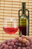 picture of loamy  - Glass bottle goblet and grape on wooden mat - JPG