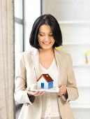 picture of possession  - picture of woman holding tablet pc with house illustration - JPG