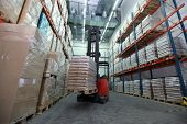 picture of forklift  - Forklift loader with pallet of sacks in distribution warehouse - JPG