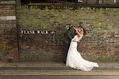 stock photo of bridal veil  - Happy couple kissing on their wedding day in front of their dream home in London - JPG