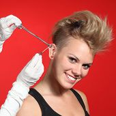 image of piercings  - Professional hands making a piercing hole to a fashion woman on a red background - JPG