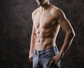 stock photo of pectorals  - A Sexy muscular man on dark background - JPG