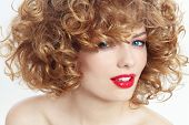 Portrait of young beautiful happy smiling woman with curly hair and red lipstick, selective focus