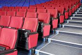 stock photo of cinema auditorium  - Rows of red and blue seats and stairs in auditorium in cinema theater - JPG