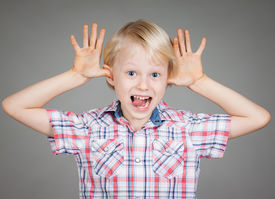 picture of cheeky  - A cute cheeky young boy smiling and sticking his fingers in his ears and pulling a funny face - JPG