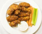 stock photo of chicken wings  - BBQ chicken wings served with celery sticks and carrots - JPG