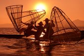 stock photo of canoe boat man  - Silhouette of traditional fishermans in wooden boat using a coop - JPG