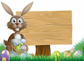 stock photo of easter card  - Easter bunny rabbit with a wooden sign holding painted Easter eggs basket - JPG
