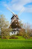 picture of wind-vane  - Traditional wooden windmill in a lush garden with four sails or blades turning in the wind to generate power and energy for farming or manufacture from the kinetic energy of the wind - JPG