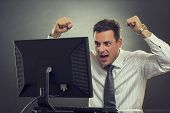 stock photo of clenched fist  - Excited businessman shouting of joy and gesturing with raised clenched fists over successful business deal in front of a computer over dark grey background - JPG