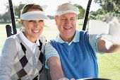 picture of buggy  - Happy golfing couple sitting in golf buggy taking a selfie on a sunny day at the golf course - JPG