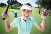 picture of ladies golf  - Lady golfer cheering at camera with partner behind on a sunny day at the golf course - JPG