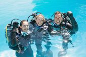 pic of oxygen mask  - Smiling friends on scuba training in swimming pool cheering at camera on a sunny day - JPG