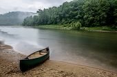 stock photo of rainy day  - Loney canoe trip on the bufflao river on a rainy day.