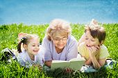 picture of tramp  - Grandmother reading a book for grandchildren outdoors - JPG
