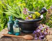 picture of essential oil  - mortar with healing herbs and sage glass bottle of essential oil outdoors - JPG