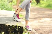 stock photo of ankle shoes  - A picture of a jogger having problems with ankle in the forest - JPG