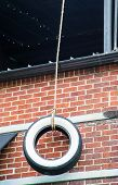image of tire swing  - A tire swing hanging from a rope by an old brick wall - JPG