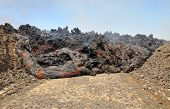 picture of magma  - Lava erupts forms stream of hot magma as it rolls down a road on the island of Fogo part of the archipelago of Cape Verde - JPG
