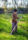 pic of scythe  - Senior farmer mowing the lawn with a scythe traditionally - JPG