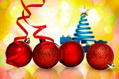 pic of girly  - Four red christmas ball decorations against girly pink and yellow pattern - JPG