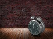 stock photo of count down  - Alarm clock counting down to twelve against room with brick wall - JPG