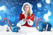 stock photo of outfits  - Pretty girl holding hands out in santa outfit against christmas scene with gifts and candy canes - JPG