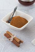 stock photo of pasteis  - Cinnamon sticks and powder on ceramic bowl - JPG