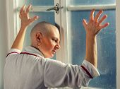 stock photo of hospital gown  - Bald woman suffering from cancer looking throught the hospital window - JPG