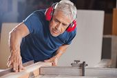 foto of carpenter  - Concentrated senior male carpenter cutting wood with tablesaw in workshop - JPG