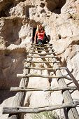 picture of cave woman  - beautiful woman climbing into caves in Bandelier national Monument in New Mexico - JPG