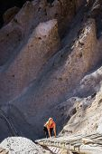 stock photo of cave woman  - beautiful woman climbing into caves in Bandelier national Monument in New Mexico - JPG