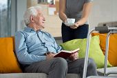 picture of geriatric  - Carer giving disabled man cup of coffee - JPG