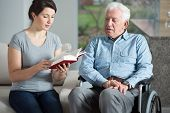 stock photo of grandpa  - Senior care assistant reading book elderly man - JPG
