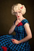 stock photo of shhh  - Pretty retro blonde woman in vintage 50s dress - JPG