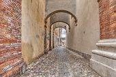 picture of ferrara  - ancient italian alley with arch and pavement of cobblestone  - JPG