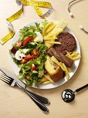 image of unhealthy lifestyle  - A plate filled half with unhealthy food and a stethoscope and the other half with fresh salad for a healthy diet and lifestyle - JPG