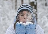 stock photo of knitted cap  - The woman is blowing about snowflakes - JPG