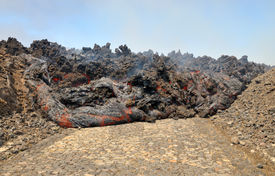 image of magma  - Lava erupts forms stream of hot magma as it rolls down a road on the island of Fogo part of the archipelago of Cape Verde - JPG