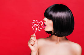 stock photo of lollipops  - model in black wig holding lollipop and posing for camera across red background - JPG