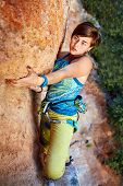 image of climbing wall  - female rock climber climbs on a rocky wall - JPG
