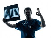 stock photo of surgeons  - one  man doctor surgeon radiologist medical gesturing okay examining lung torso x - JPG