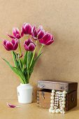 picture of mother-of-pearl  - Bright purple flowers in a white vase tulips and wooden chest with pearls - JPG