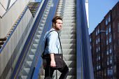 foto of escalator  - Portrait of a young guy with bags walking up escalator - JPG