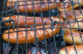 picture of grilled sausage  - Barbecue with fiery sausages on the grill - JPG