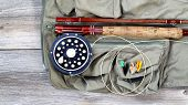 image of vest  - Antique fly fishing reel and rod with vest and flies on rustic wood - JPG