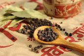 stock photo of bay leaf  - Wooden spoonful of black pepper seeds and bay leaves on ethnic cloth  - JPG