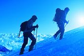 foto of mountain-climber  - climbers at the top of a pass with backpacks meeting the sunrise in the mountains - JPG